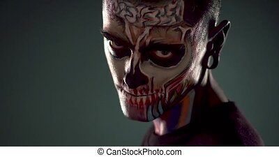 Man with colored skeleton face showing evil smile.