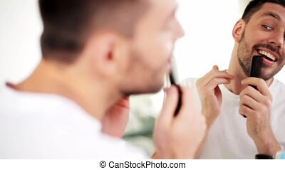 man with comb looking to mirror and singing - beauty,...