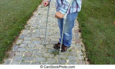 Man with crutches on cobbled path