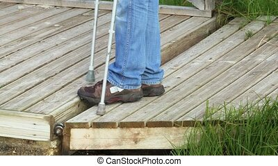 Man with crutches on wooden bridge surface