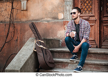 Man with cup of coffee sitting on the building stairs