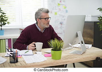 Man with cup of coffee working on computer