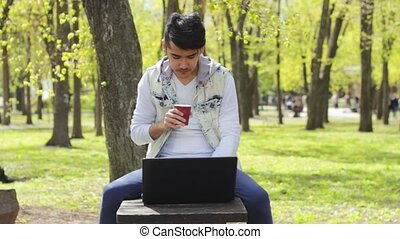 Man with cup of coffee working on laptop