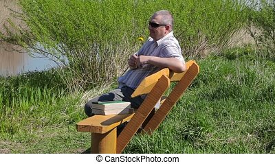 Man with dandelion relax on bench