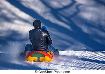 Man with daughter sledding down a snowy hill
