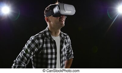 Man with delight watching in virtual reality glasses. Black studio