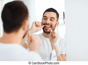 man with dental floss cleaning teeth at bathroom - health...