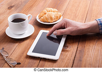 Man with digital tablet croissants and coffee on a wooden table.