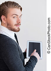 Man with digital tablet. Rear view of handsome young man holding a digital tablet and looking over shoulder while standing against grey background