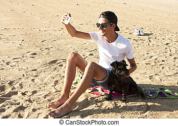 man with dog at the beach pulling a picture with the mobile phone. Sunset warm light summer