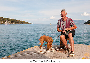 Man with dog in harbor