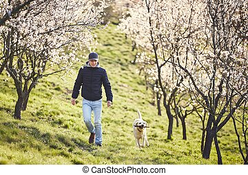 Man with dog in spring nature