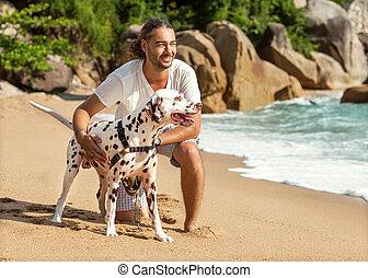 man with dog on the beach
