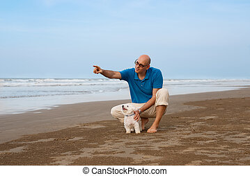 Man with dog pointing to something at the beach