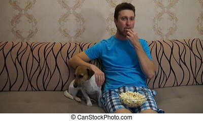 Man with dog watching tv