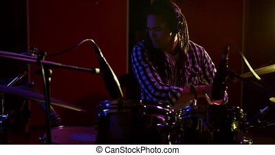 Man with dreadlocks playing drums in a music studio