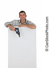 Man with drill leaning on a white sign