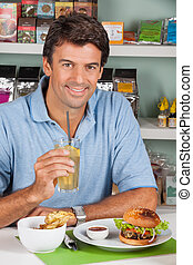 Man With Drink And Burger In Supermarket - Portrait of mid...