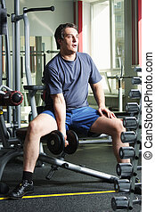Man with dumb-bell - Man in shirt and shorts at gym with...