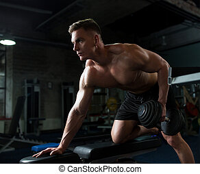 man with dumbbell and bench exercising in gym