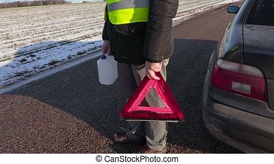 Man with empty can and warning triangle near car on the road