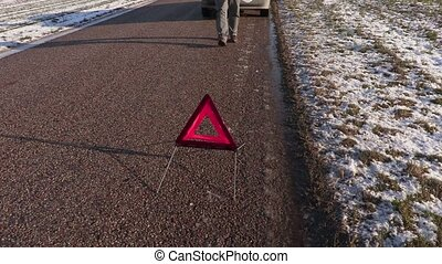 Man with empty can near warning triangle on the road