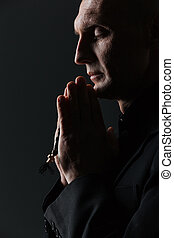 Man with eyes closed holding rosary and praying over black...