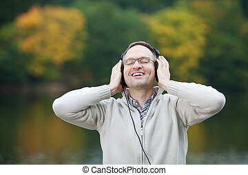 Man With Eyes Closed Listening To Music Against Lake