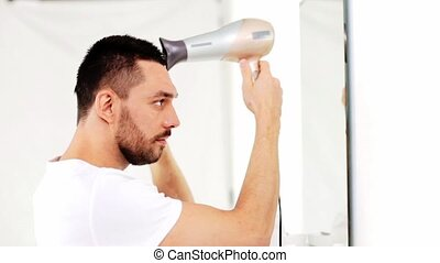 man with fan drying his hair at bathroom