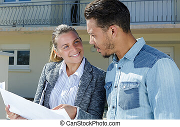 man with female real estate agent near house