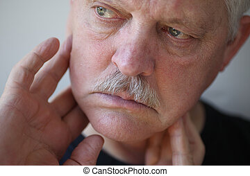 Man with fingers on painful jaw - senior man touches his...