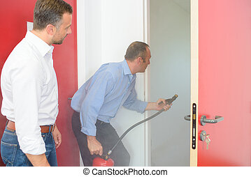 Man with fire extinguisher at doorway of smoke filled room