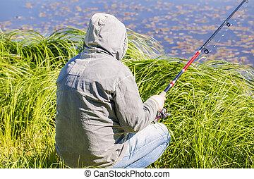 Man with fishing rod at the lake