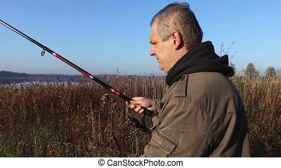 Man with fishing rod near the lake