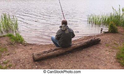 Man with fishing rod sitting near lake
