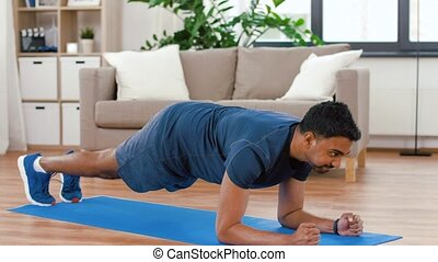 man with fitness tracker doing plank at home - sport, ...