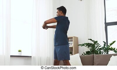 man with fitness tracker stretching waist at home - sport...