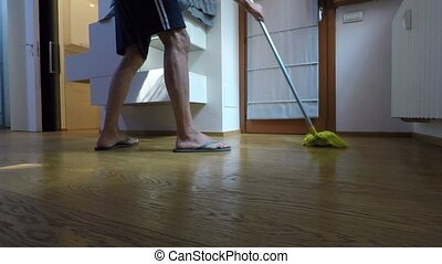 Man with flip-flops and shorts washes the floor in the...
