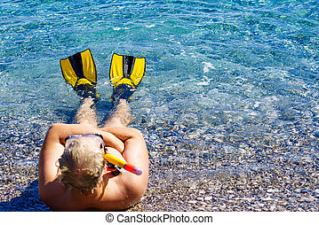Man with flippers snorkeling tube on beach