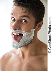 Man with foam on face showing his tonque