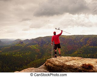 Man with forearm crutch. Hiker achieved mountain peak with broken leg in immobilize