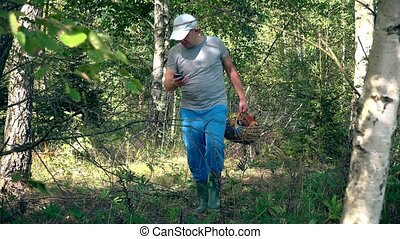 Man with full basket of mushrooms looking for his GPS signal on smartphone