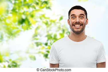 man with funny face over green natural background
