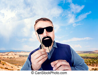 Man with funny sunglasses and beard on a stick