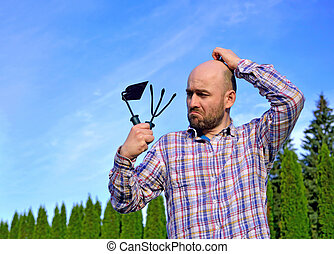 man with garden tools in park