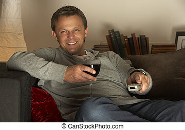 Man With Glass Of Wine Watching Television