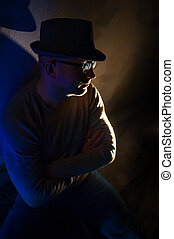 man with glasses and a hat sitting in the dark