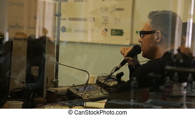 Man with glasses and a light stubble holds microphone and...