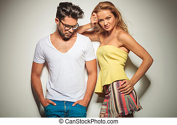 man with glasses and hands in pockets looks down while woman is holding her head