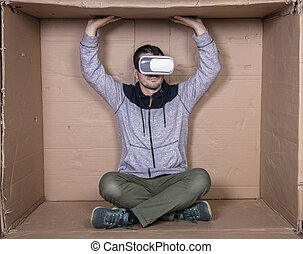man with glasses for virtual reality, sitting in a cardboard room and entertained